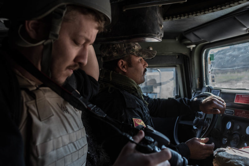 American freelance journalist Igor Kossov rides with an Iraqi special forces soldier in an armored vehicle in Mosul on January 17, 2017.